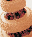 Tiered white wedding cake with fresh berries