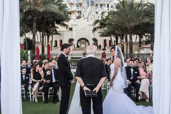 bride and groom with pastor at acqualina resort & spa outdoor wedding on lawn