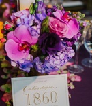 Table card with pink and purple bouquet at wedding