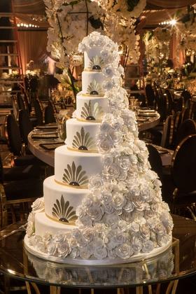 Art deco design wedding cake gold white cascading sugar flowers rose frosting on glass table wedding