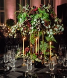 Tall centerpiece of unstructured greenery and oxblood flowers tall taper candles in gold black linen