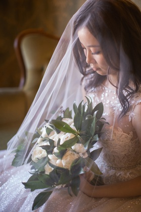 asian bride wearing blusher veil draping delicately over the bridal bouquet