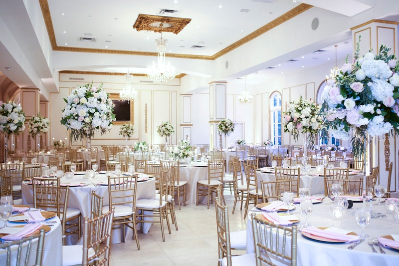 Ballroom reception with gold details round tables with linens gold chairs pink napkins tall flowers