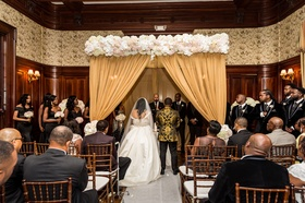 indoor ceremony with dark wood wainscoting, ceremony altar with white and blush flowers, gold drape