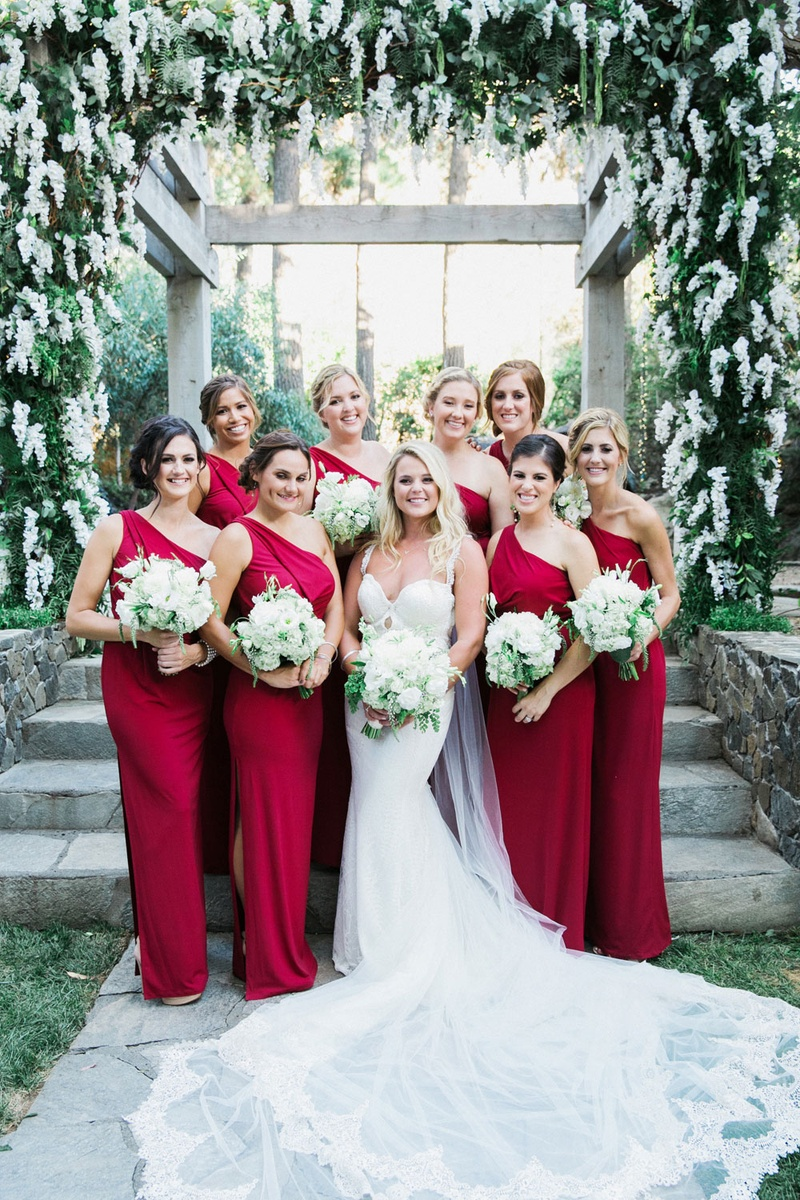 bride in galia lahav, bridesmaids in scarlet one-shoulder dresses with a high slit