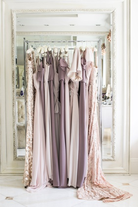 bridesmaid dresses in shades of light purple on clothing rack in front of mirror bridal suite