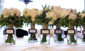 White flower bouquet with greenery in vases
