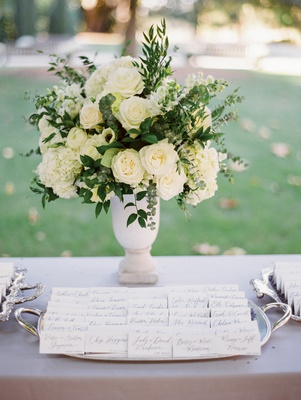 escort cards displayed on silver tray in front of ivory roses with greenery in vase