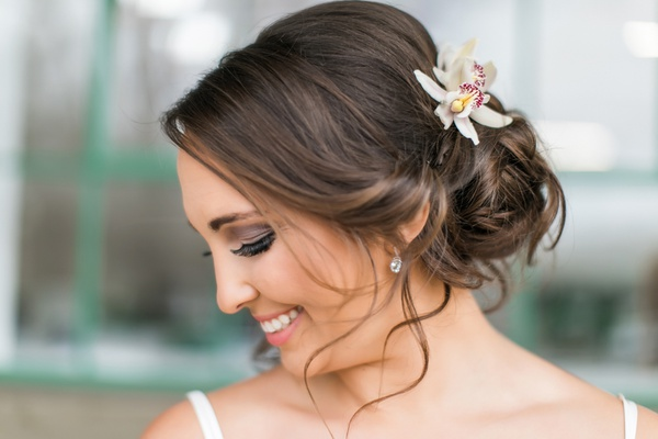 brunette bride with low bun and soft tendrils, orchids in hair