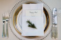 Sprig of greenery on top of wedding napkin and menu on charger plate place setting