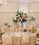 wedding centerpiece with white roses and greenery, pale blue glasses, gold chiavari chairs