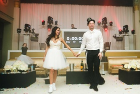 Bride in short overskirt and bridal sneakers with groom in New Year's Eve party hat by countdown