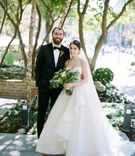 Bride in strapless a line ball gown Peter Langner wedding dress groom in tuxedo bow tie green flower