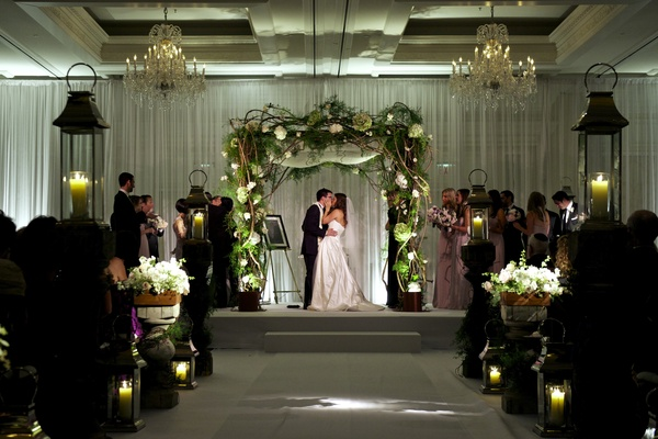 Bride and groom kissing under rustic chuppah