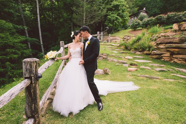 Man in tuxedo and woman in wedding dress in grass