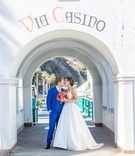 bride and groom kiss under arch in beach wedding