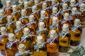 Farm wedding reception diy favors of herb olive oil in corked glass bottles, white ribbons