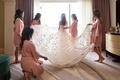 bride in galia lahav wedding dress embellished skirt in sun help from bridesmaids in pink robes