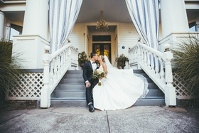 bride in stella york kissing groom on porch steps of white house napa valley inn