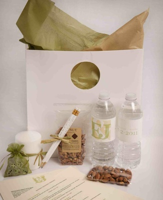 Green and white wedding guest bag with almonds and water bottles