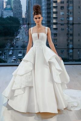 Sleeveless natural waist ball gown with split neckline, contoured straps, ruffled overskirt adorned