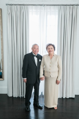 couple celebrating 50th anniversary, woman in ivory st. john outfit man in ralph lauren purple label