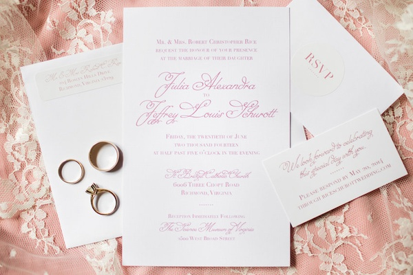 Pink calligraphy on invitations for wedding atop pink lace