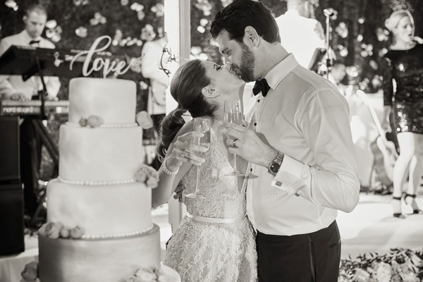 Black and white photo of bride and groom with champagne kissing after cake cutting laser cut topper