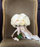Wedding bouquet with white roses tied with pink ribbon