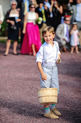 Boy in short pants with suspenders and white shirt holds basket at country wedding