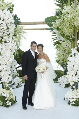 Bride and groom under bamboo and orchid chuppah
