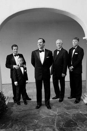 Black and white photo of groom with male guests in tuxes