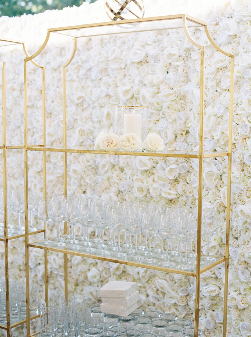 flower wall of ivory roses, gold stand displaying wine glasses at wedding reception