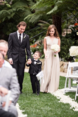 ring bearer holds hands with groomsman in kenneth cole and bridesmaid in tan bhldn dress