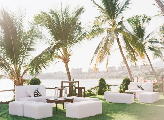 Wedding cocktail hour reception grass lawn white seating lounge areas wood tables minimal