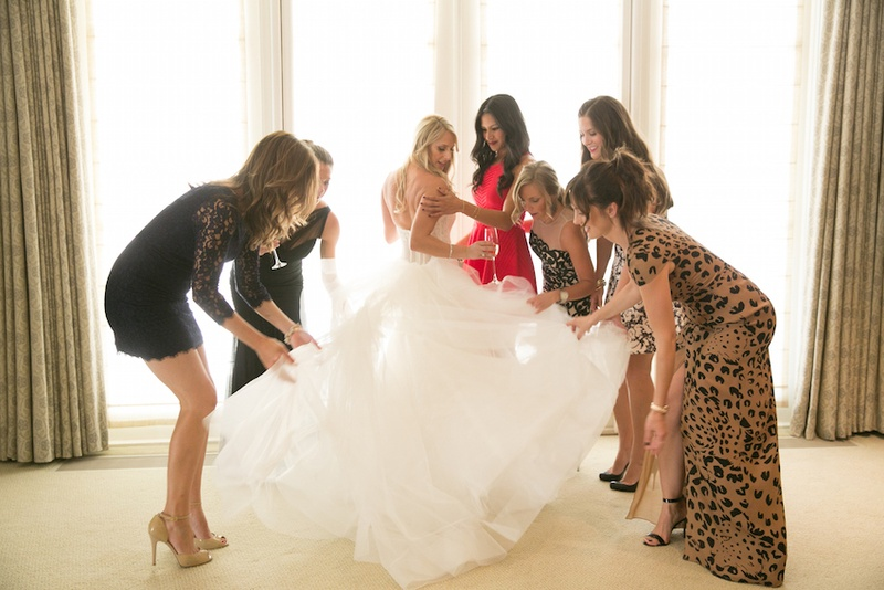 Women help bride with ruffles on wedding dress