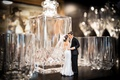 wedding cake topper bride in dress with veil groom in suit next to bar decanter glasses