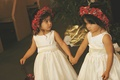 Two flower girls hold hands in white dresses and red flower crowns