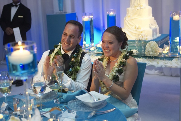 newlyweds wear flower leis while seated at table