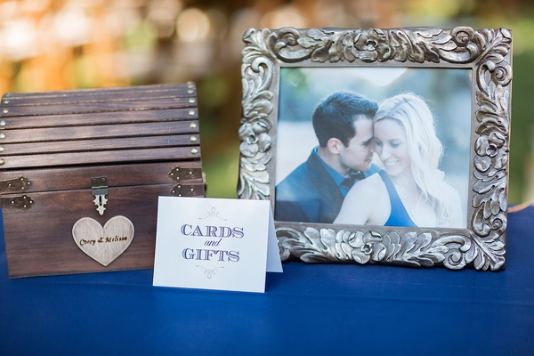 Outdoor wedding reception gift table covered in royal blue tablecloth, wood chest, framed photo