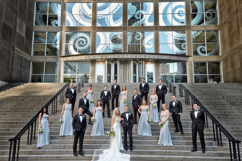 Bride and groom with groomsmen in suits and bridesmaids in long light blue bridesmaid dresses