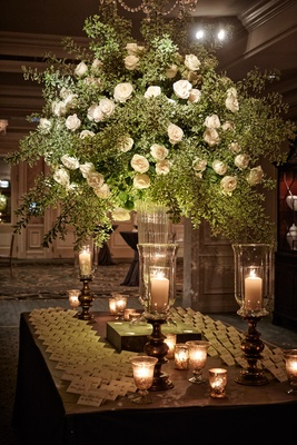 Wood escort card table with seating assignments and tall greenery arrangement with white flowers