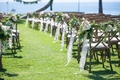 Oceanfront wedding with pink, peach, white flowers, greenery, lace on wood chairs along aisle