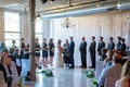Bride and groom at altar under exposed ceiling