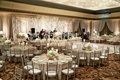Wedding reception with silver chiavari chairs, white, pink, and green centerpieces, band, draping