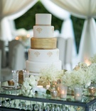 White and gold wedding cake on crystal table white flower bouquets champagne flutes