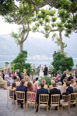 Guests seated around bride and groom at outdoor Italian ceremony