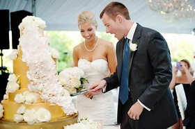 Bride and groom cut into gold cake with white sugar flowers