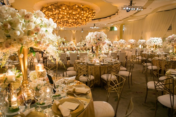 Round reception tables with mirror tops, gold centerpiece, rose orchid flowers, chameleon chairs