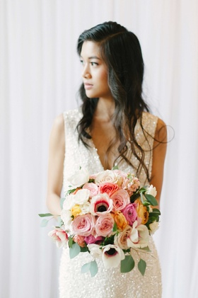 a bride in a shimmery gown holds a colorful bouquet of white pink and yellow flowers with greenery